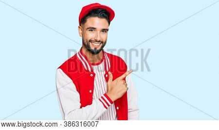 Young man with beard wearing baseball uniform cheerful with a smile of face pointing with hand and finger up to the side with happy and natural expression on face