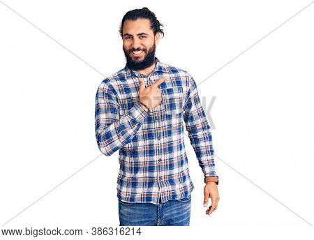 Young arab man wearing casual clothes cheerful with a smile of face pointing with hand and finger up to the side with happy and natural expression on face