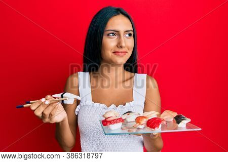 Young brunette woman eating butterfish sushi using chopsticks smiling looking to the side and staring away thinking.