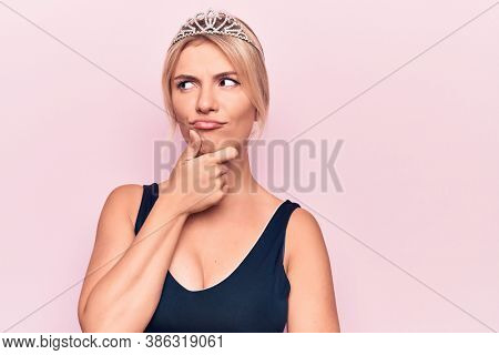 Young beautiful blonde woman wearing princess crown over isolated pink background thinking concentrated about doubt with finger on chin and looking up wondering