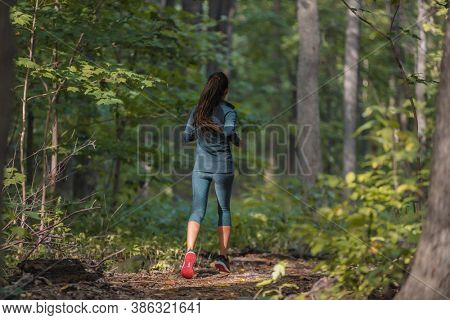 Autumn run athlete training outdoors in forest trail nature. Runner jogging from behind in fall season sportswear clothes.