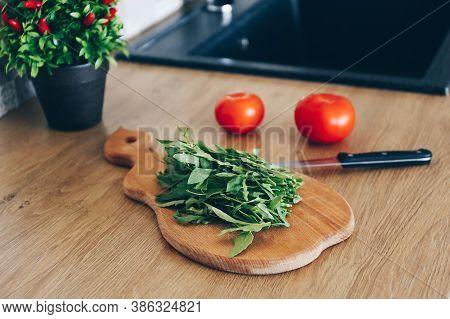 Fresh Organic Arugula Leaves On Cutting Board. Arugula Or Rucola For Salad On Wooden Table.