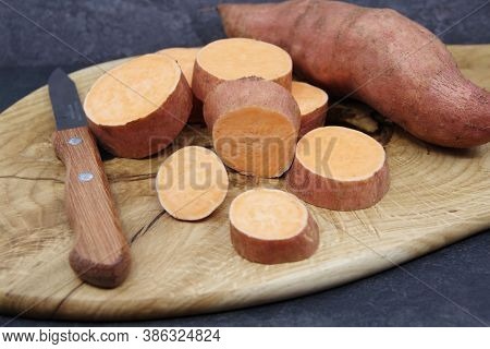 Sweet Potatoes On A Wooden Cutting Board. Organic Sweet Potato For Healthy Eating. Closeup