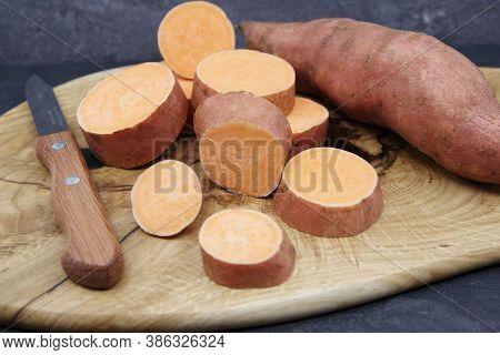 Sweet Potatoes On A Wooden Cutting Board. Organic Sweet Potatoes For Healthy Eating. Closeup