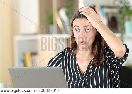 Stressed Woman Discovers Mistake On Laptop Sitting In A Desk At Home