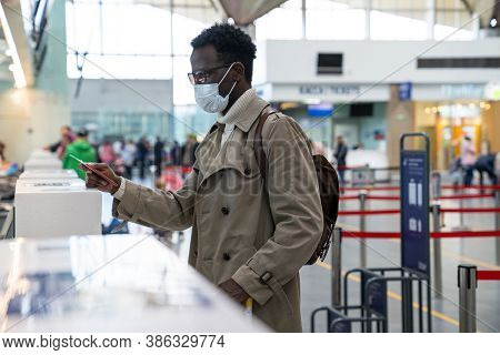 African American Man Stands At Check-in Counters At The Airport Terminal, Giving Passport To An Offi