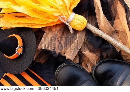Orange And Black Halloween Flatlay. Witch Clothes: Stockings, Boots, Hat, Broom, Skirt