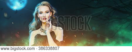 Halloween. Enchanting young woman witch on the background of a night forest and a full moon, surrounded by magic lights. Copy space.