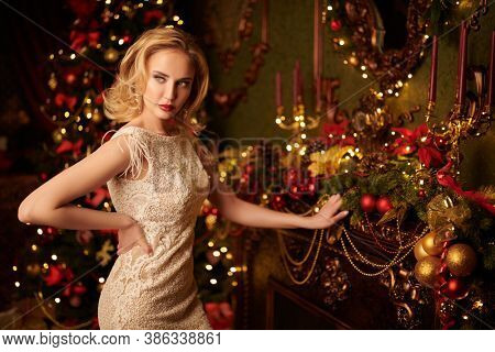 Fashionable young woman wearing luxurious evening dress and with beautiful evening makeup and hairstyle in the fairy beautiful Christmas interior.