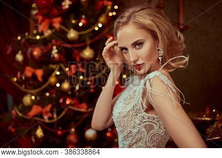 Fashionable young woman wearing luxurious evening dress and with beautiful evening makeup and hairstyle in the fairy beautiful Christmas interior. Christmas tree in the background. Jewellery.