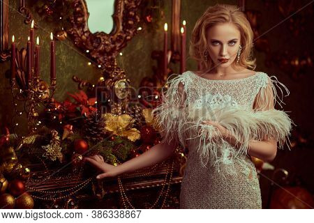 Christmas and New Year magic. Charming happy young woman in a festive evening dress and with beautiful evening makeup and hairstyle in the fairy beautiful Christmas interior.