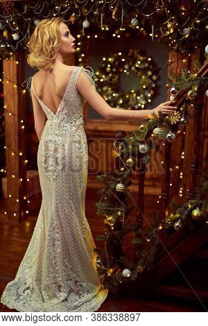Christmas and New Year celebration concept. Charming young woman in luxurious evening dress and with beautiful evening makeup and hairstyle meets Christmas at the New Year tree.