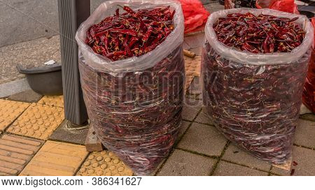Two Large Plastic Bags Full Of Red Chile Peppers For Sale Sitting On Sidewalk At Open Air Market.
