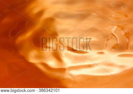 Macro Shot Of Water Ripples In Golden Orange Color.