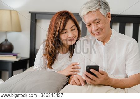 Asian Senior Couple Using Mobile Phone At Home. Asian Senior Chinese Grandparents, Husband And Wife