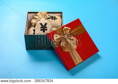 Side View Gift Box Full With Rmb Money Bags On Blue Background