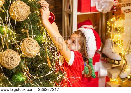 Christmas Toy - Girl Is Decorating The Christmas Tree. Christmas Kid Decorating Christmas Tree With