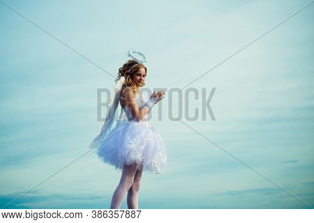 Charming Curly Little Girl In White Dress And Wings - Angel Cupid Girl. Enjoying Magic Moment. Teena