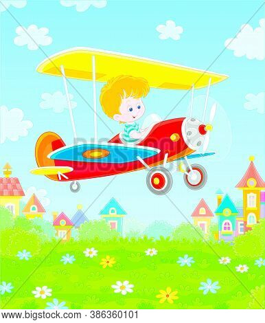 Little Cheerful Boy Piloting His Small Toy Plane Among White Clouds In Blue Summer Sky Over A Green