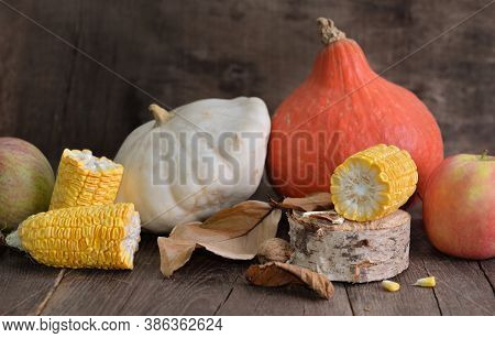 Various And Colorful Autumnal Vegetables And Fruits And Cob Of Corn Cut Into Pieces On Wooden Backgr