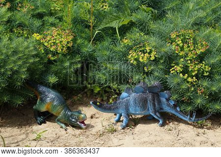 Dinosaurs On A Background Of Green Grass. Toy Stegosaurus And Tyrannosaurus Rex Are Standing On The