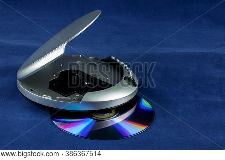 Cd And Portable Cd Player Isolated Against A Blue Background