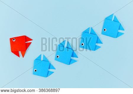 Red Origami Paper Fish Changing Direction While Swimming Ahead Of Line Of Blue Fish. Concept For New