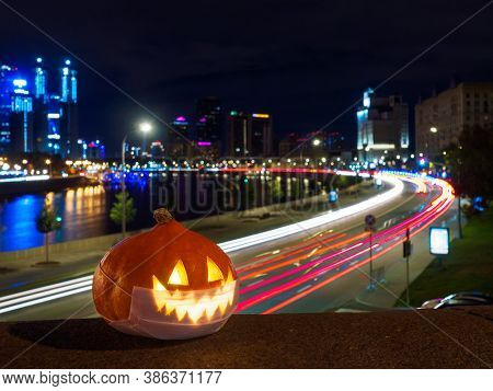 Halloween Pumpkin With Protective Face Mask At Night. Skyscrapers, River And And Streaks Of Light Fr