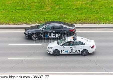 White And Black Passenger Car Uber Taxi Rides On The Highway Aerial View. Russia, Saint-petersburg.