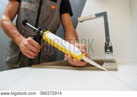 Worker Seals Kitchen Sink With Sealant. Hands Of Worker Works With Construction Sealant Gun In The K
