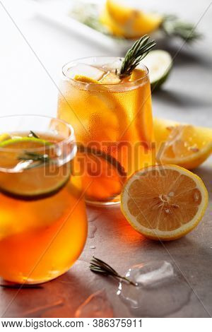 Traditional Iced Tea With Lemon, Lime And Ice Garnished With Rosemary Twigs. Selective Focus.