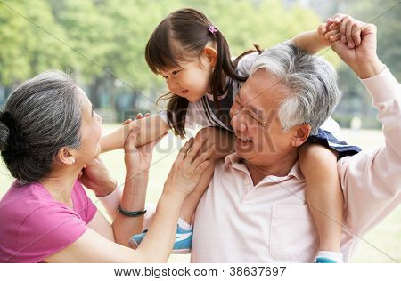 Chinese Grandparents Giving Granddaughter Ride On Shoulders