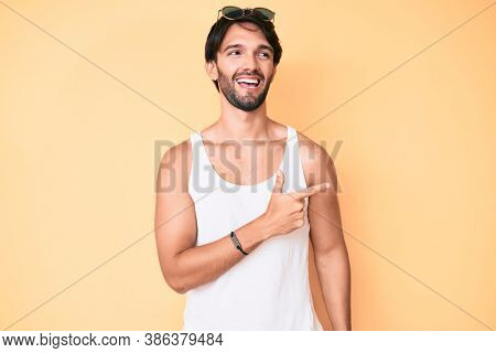 Handsome hispanic man wearing summer look and sunglasses cheerful with a smile of face pointing with hand and finger up to the side with happy and natural expression on face
