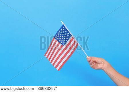 Womans Hand Holding Small American Flag On Blue Background. Space For Text.