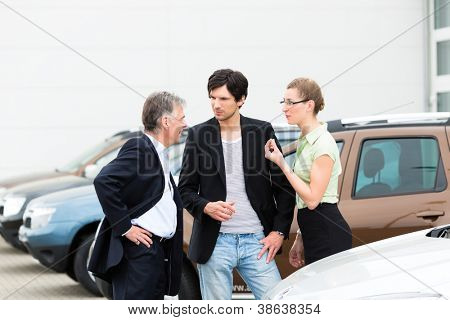 Mature man and young couple standing on a parking place standing in the middle of cars, obviously they are in a sales pitch