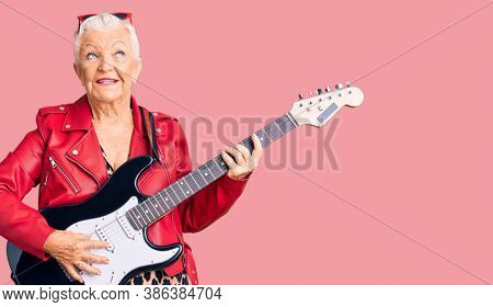 Senior beautiful woman with blue eyes and grey hair wearing a modern look playing electric guitar smiling looking to the side and staring away thinking.