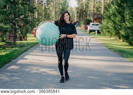Young Fit Brunette Woman Holds Big Fitness Ball, Dressed In Active Wear, Does Exercises Workout, Pos