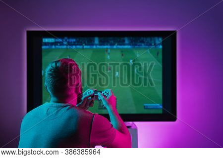 Back View Shot Of Professional Gamer Playing Online Video Game On His Gameset. Room Lit In Neon Ligh