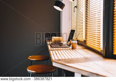 Computer Laptop With Coffee Cup And Open Book On The Modern Wooden Table On The Kitchen Near Big Win
