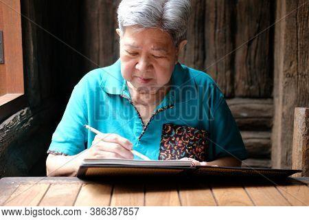 Asian Elderly Female Elder Woman Writing Note At Home. Senior Leisure Lifestyle