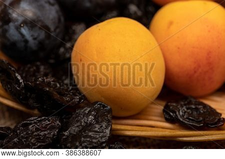 Ripe Apricots, Juicy Black Plums And Dried Prunes In A Wicker Basket. Close Up. Autumn Harvest.