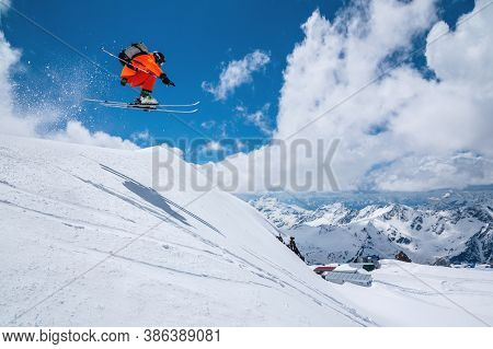 Man Skier Athlete Makes A Jump In Flight On A Snowy Slope Against The Backdrop Of A Blue Sky Of Moun