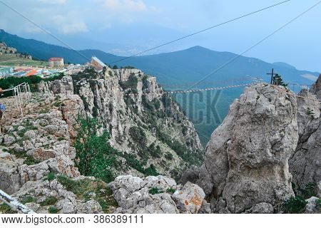Hanging Suspension Bridge Over An Abyss In Steep Rocks Ai-petri, Crimea. Cliff Against The Backdrop