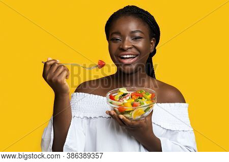 Healthy Nutrition. Happy Black Young Woman Eating Fresh Vegetable Salad With Fork, Holding Bowl With