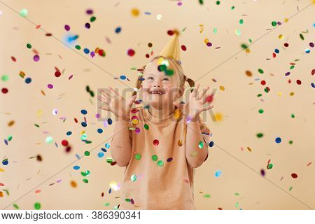 Waist Up Portrait Of Excited Girl With Down Syndrome Smiling Happily While Standing Under Confetti S