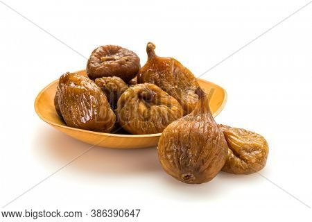 Preserved fruit. Dried figs in small wooden bowl isolated on white background.