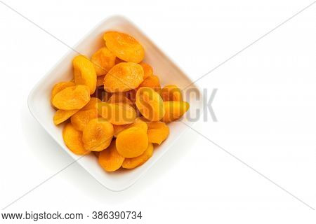 Preserved fruit. Dried sulfurized apricots in square white bowl isolated on white background with copy space. High angle view