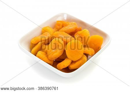 Preserved fruit. Dried sulfurized apricots in square white bowl isolated on white background.