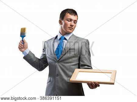 Creative Businessman Painter Holding Paint Brush And Whiteboard In Hands. Portrait Of Handsome Young