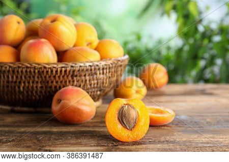 Many Fresh Ripe Apricots On Wooden Table Against Blurred Background